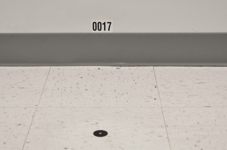 A test point on the floor of a building at NIST for testing indoor localization systems and the associated ID on the wall